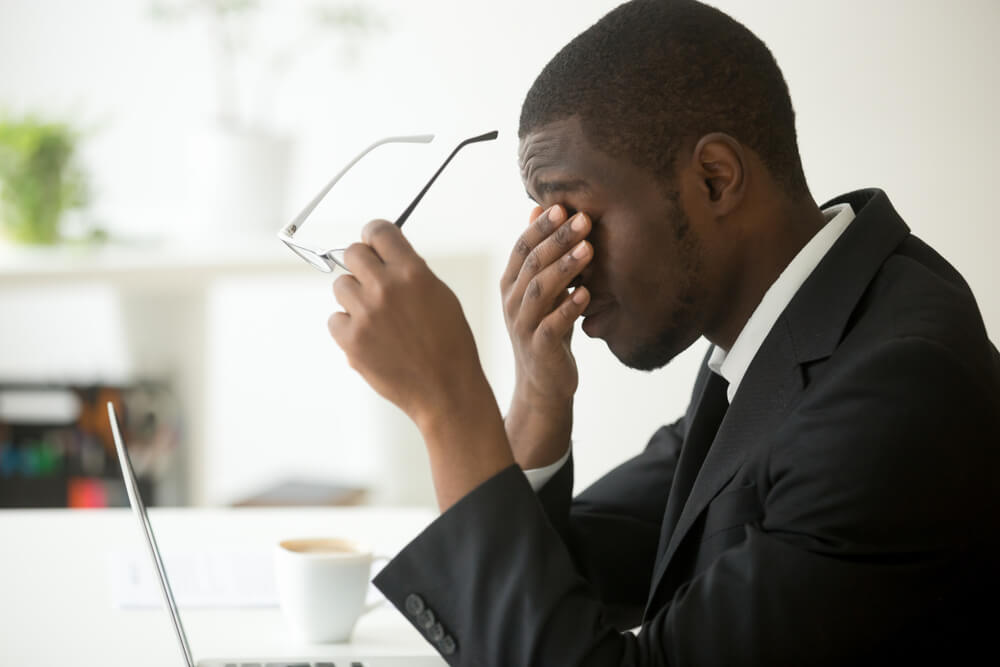 man sitting in front of laptop rubbing eyes from fatigue and jetlag