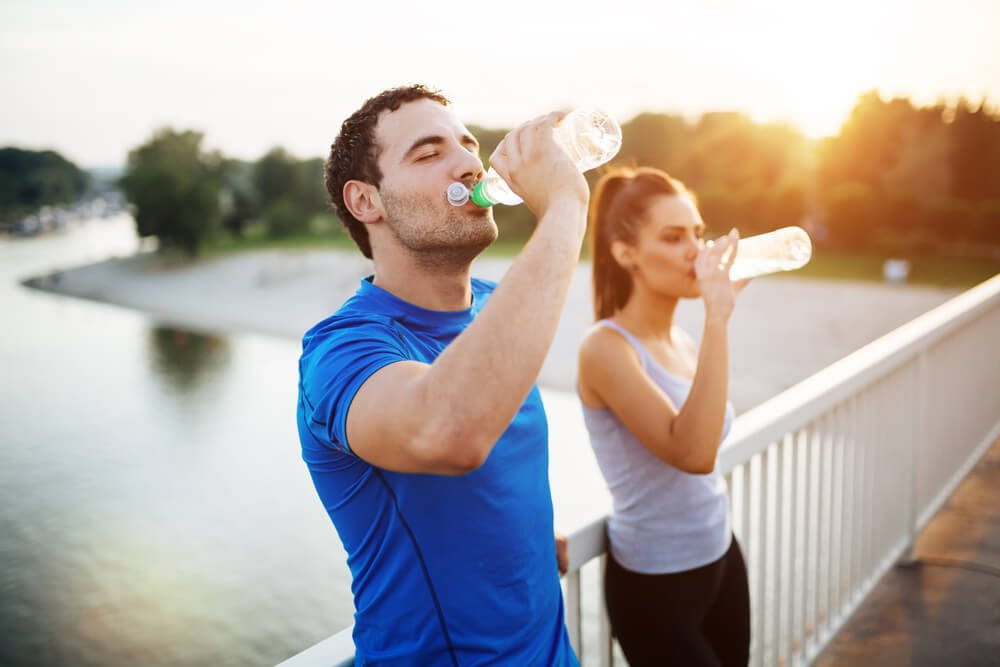 couple staying hydrated together after workout